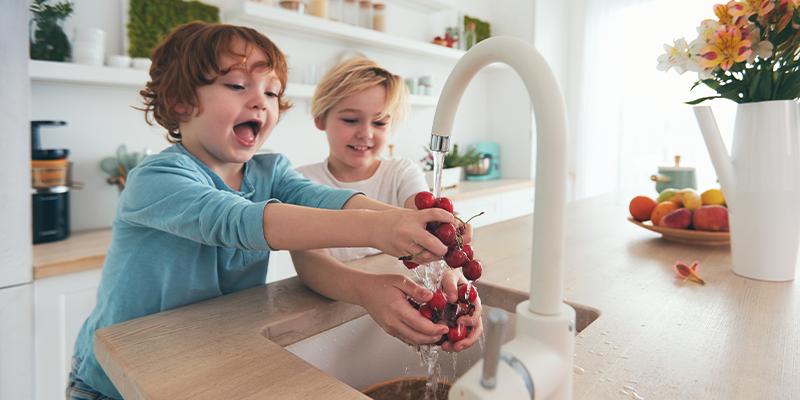 Kinder waschen Obst unter Leitungswasser